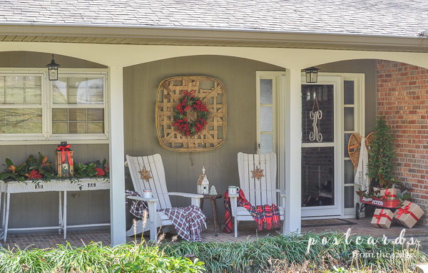 white wicker table, adirondack chairs, red radio flyer wagon with Christmas decor on front porch