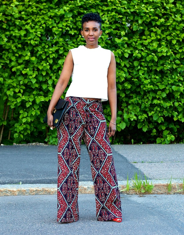 street style photo of woman with a white top, african print palazzo pants and a pair of red heels is striking a pose