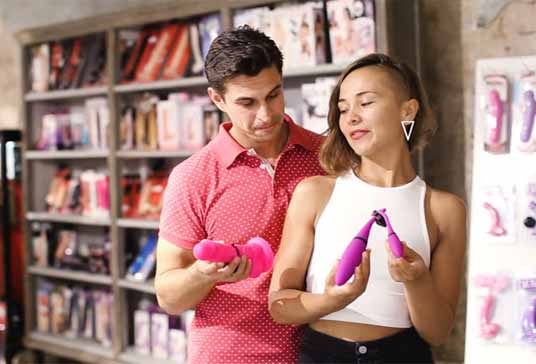 A man in red shirt standing next to a woman in white shirt in a sex store with some sex equipment in their hands