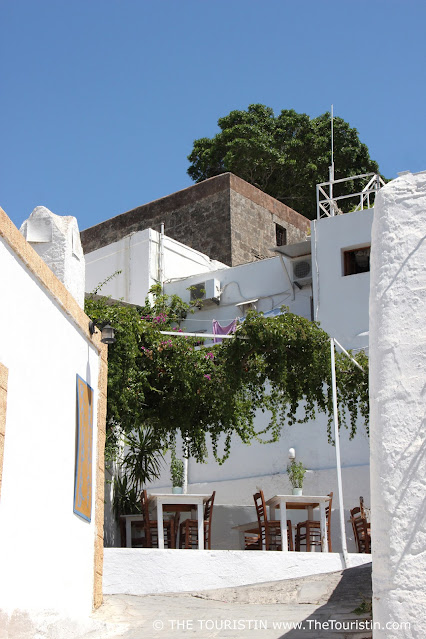 Wooden white washed tables and chairs, overgrown by wine, set in a lane between whitewashed houses under a deep blue sky.