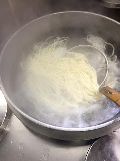 手打ちうどんを、揚げざるでかき混ぜる。