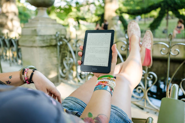Close up of a person with tattoos and bracelets reading from an ebook reader.