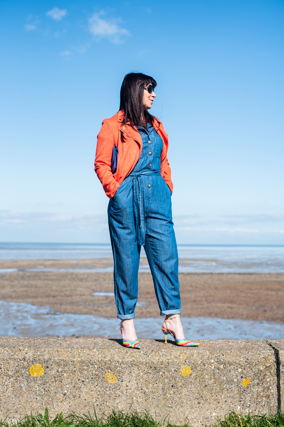 Staring out to sea mid life blogger Jacqui Berry from Mummabstylish in denim boiler suit and orange jacket