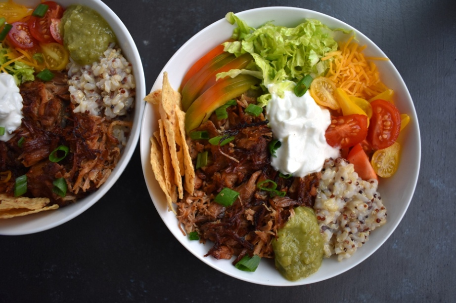 Carnitas Burrito Bowls feature crispy, flavorful pork carnitas, brown rice, cheddar cheese, tomato, green onion, chips, bell peppers and more for a fresh, filling meal ready in about 30 minutes! www.nutritionistreviews.com #mexicanfood #mexican #burrito #pork #dinner #easydinner