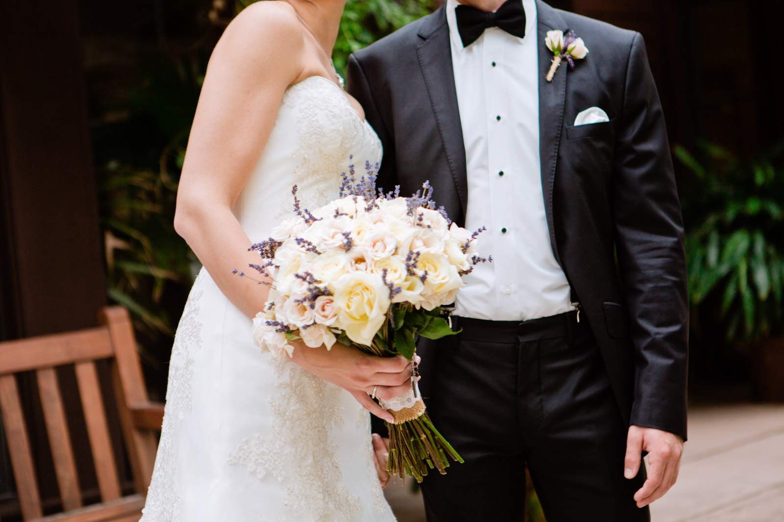 a bride and groom hold a ivory and purple bridal bouquet