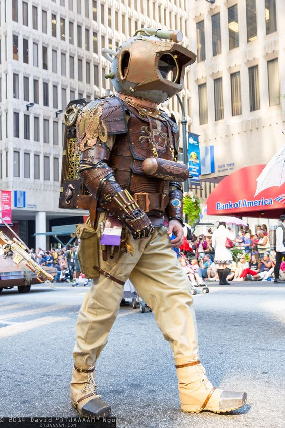 Man dressed as a steampunk diver with an underwater leather armor and gold diving helmet.
