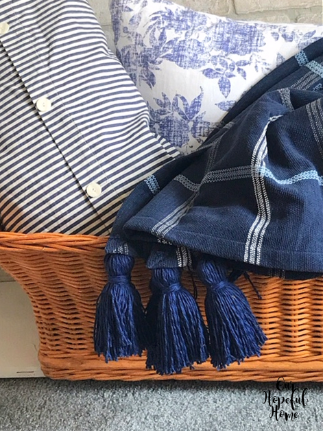 three blue yarn tassels hanging over side of basket and blue striped pillow