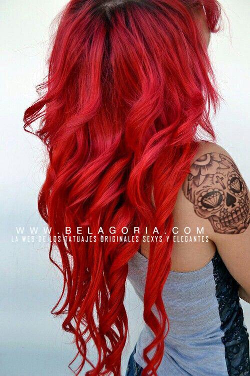 Vemos a chica de pelo largo rojo esta de espaldas y en su hombro el tatuaje de una calavera mexicana