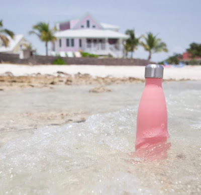Pink S'well bottle on the beach