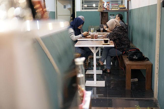 Pengunjung bersantai di area dalam kedai kopi