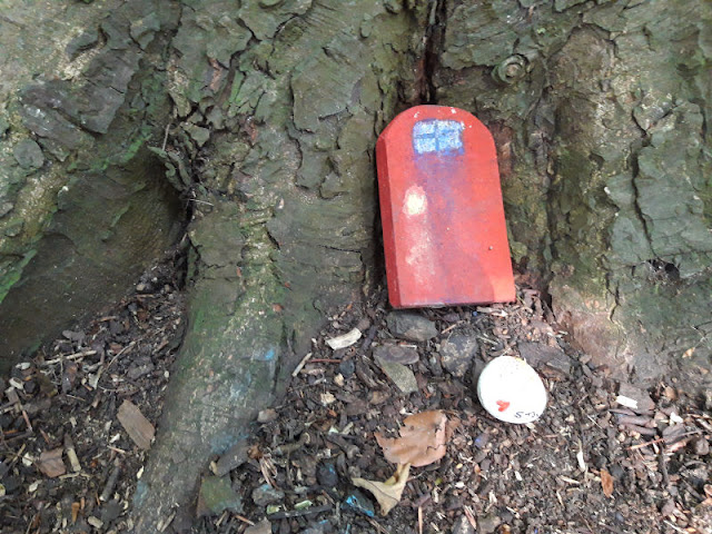 A red fairy door against a tree truck. There is a painted pebble in front of the door.