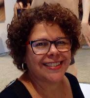 Mulher de cabelos cacheados, usando óculos