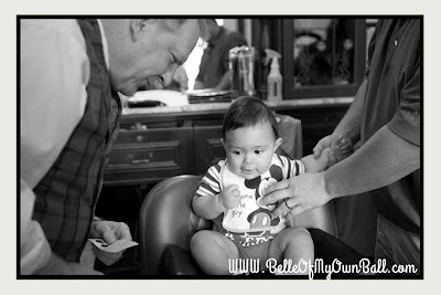 A photo of a baby anticipating being tickled while receiving his first haircut at Harmony Barber Shop in the Magic Kingdom.