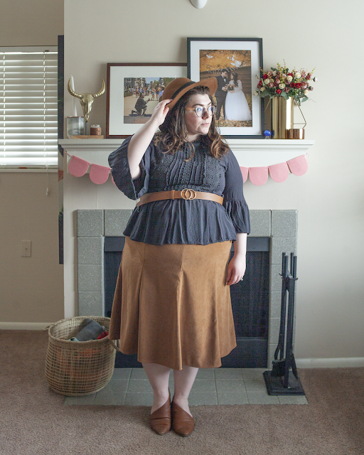 An outfit consisting of a brown panama hat, black Victorian inspired blouse over a brown maxi skirt and brown d'orsay flats.