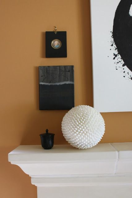 Pumpkin orange wall with black seascape painting by Michele of Hello Lovely