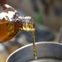 Image of golden oil being poured from a glass bottle