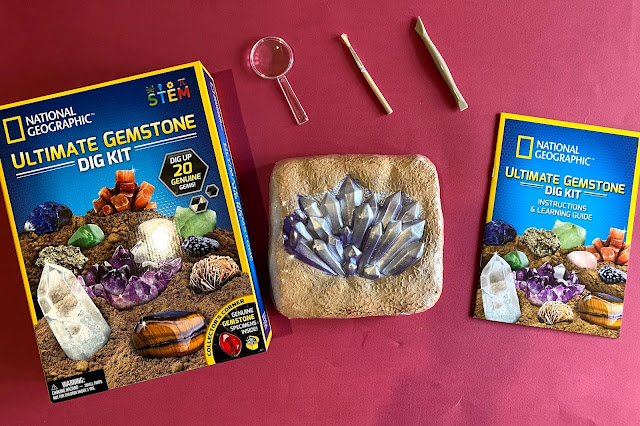 Contents of the Ultimate Gemstone Dig Kit includes a block with 20 gemstones, digging tool, brush, magnifying glass, instructions and learning guide.
