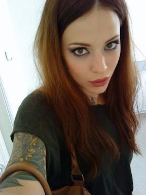 chica peliroja nos mira mientras se hace un selfie, lleva tatuajes muy sexis en los brazos y cuello