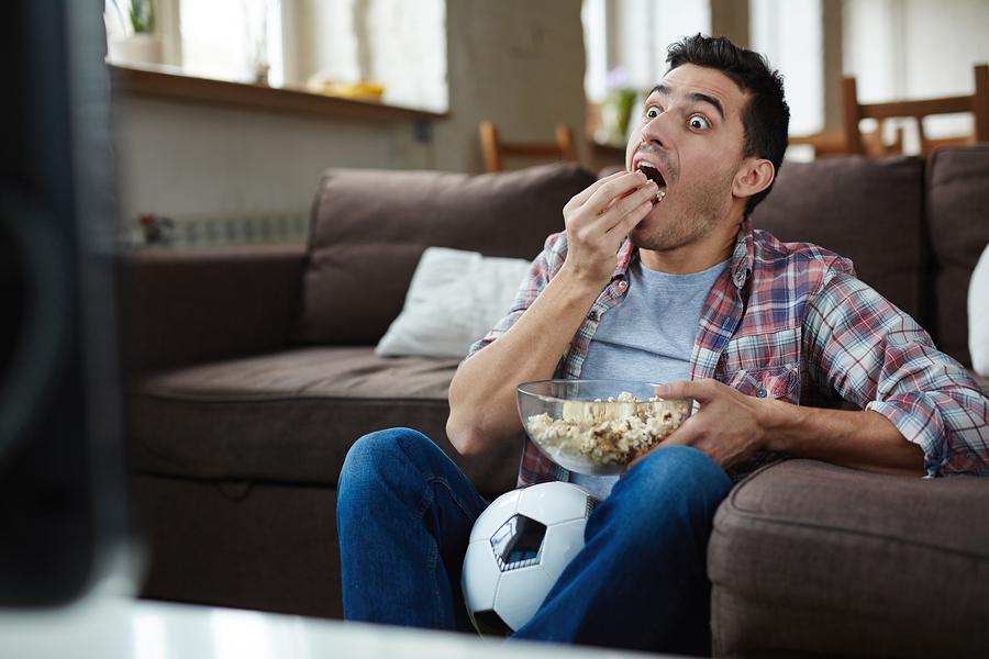 pemuda makan sambil nonton tv