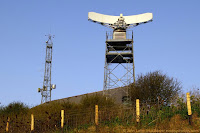 Situated on the White Cliffs of Dover overlooking the English Channel. Microwave tower, or mast on the left, radar scanner, or antenna on the right. Low roof of the operations room (control center) is in the middle.