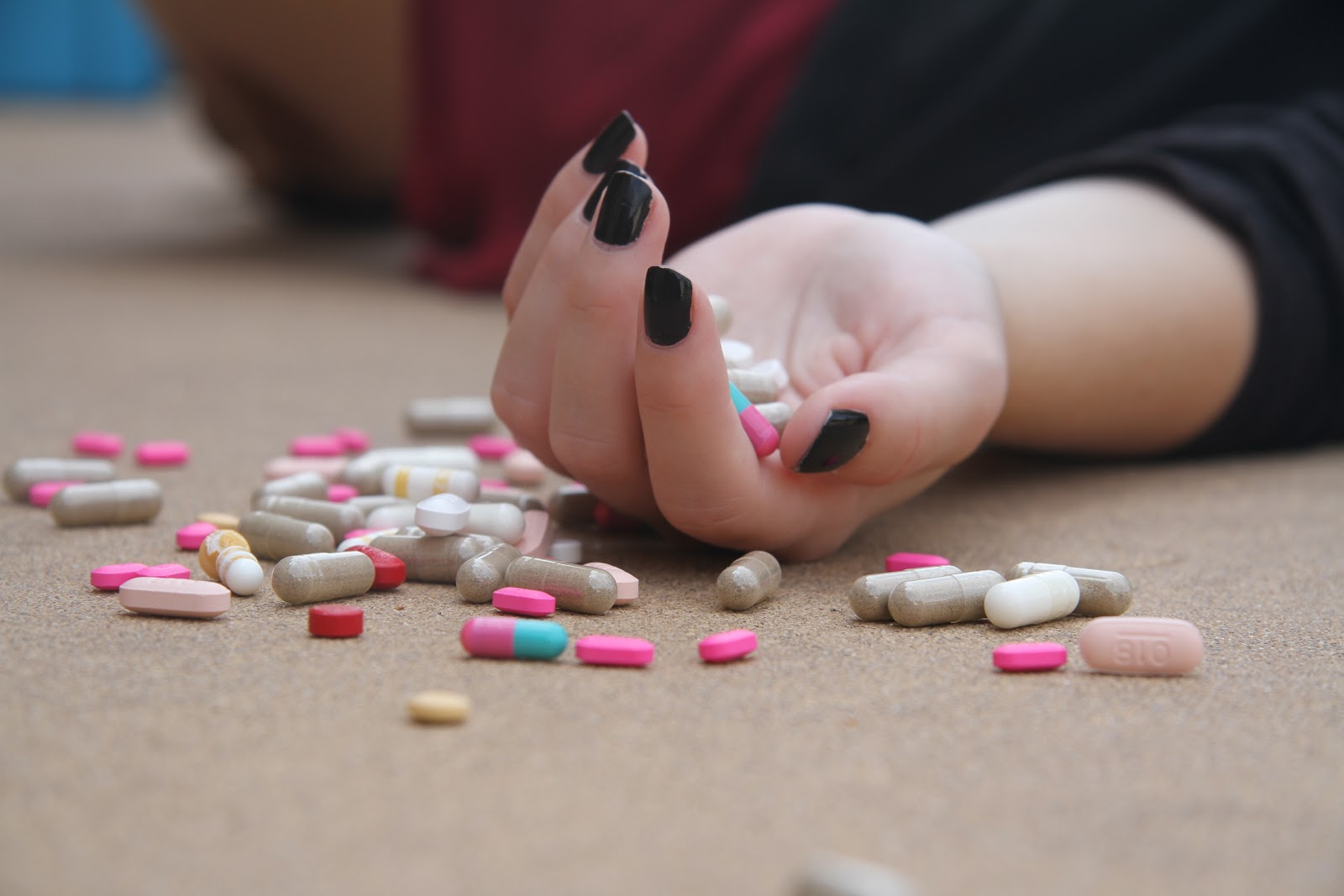 机の上で黒いマニキュアの左手から多くの明るい色の錠剤が溢れている