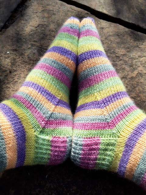 Image shows a pair of feet wearing socks knitted in The Yarn Badger yarn.  The soles of the feet are touching so that the stripes match up