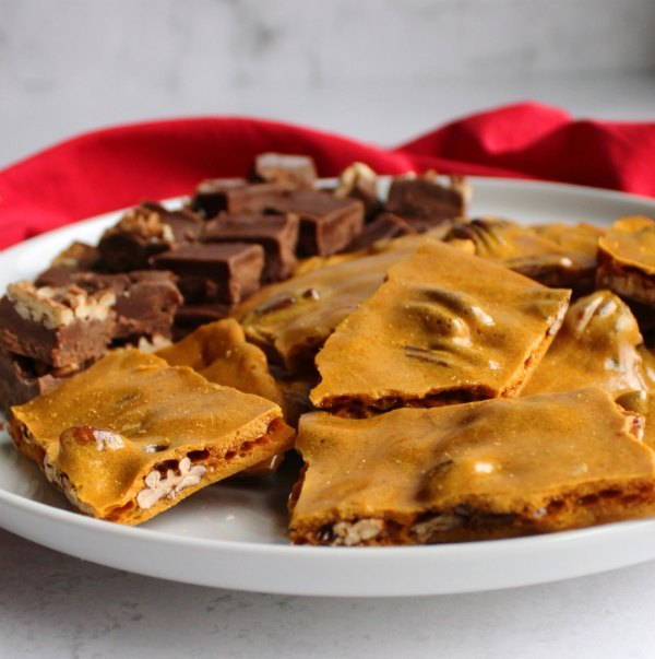 golden pecan brittle on plate with squares of fudge