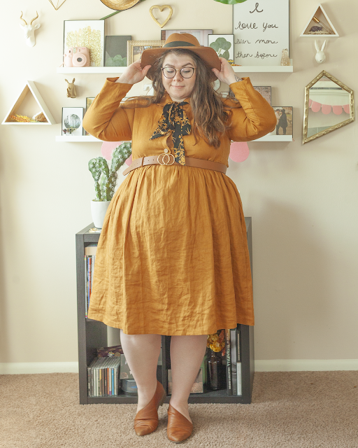 An outfit consisting of a brown panama hat, a yellow ochre long sleeve collared baby doll linen midi dress and brown d'orsay flats