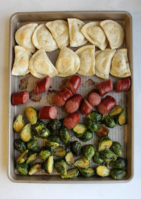 cooked pierogi, hunks of sausage and halved brussels sprouts on sheet pan