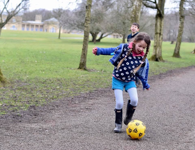 girl playing football in Heaton Park, Manchester