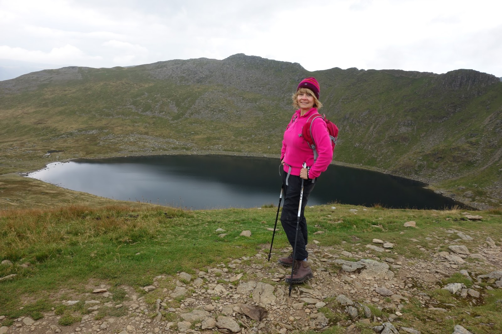 Gail Hanlon from Is This Mutton? after climbing Helvellyn and Striding Edge, in pink North Face fleece and Sherpa hat