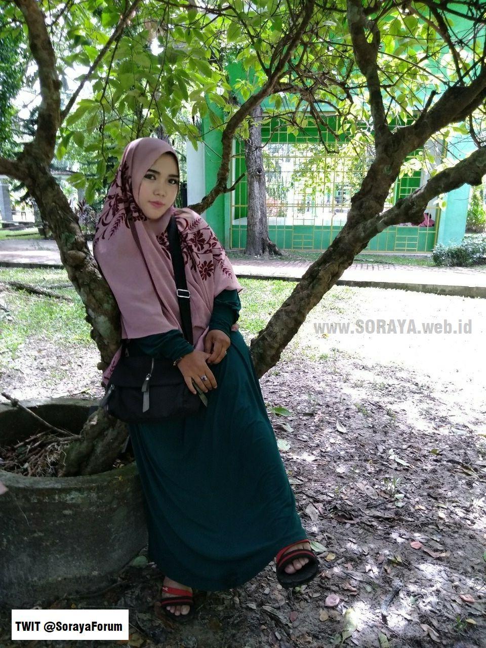 photo soraya wanita berjilbab duduk sendiri di dahan pohon
