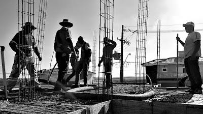 Equipe de pedreiros concreta uma laje.