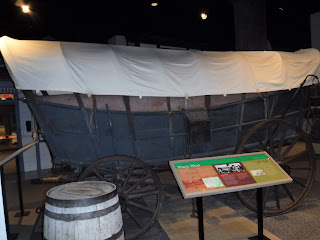 a covered wagon and wooden barrels on display at the Durham Museum in Omaha, Nebraska