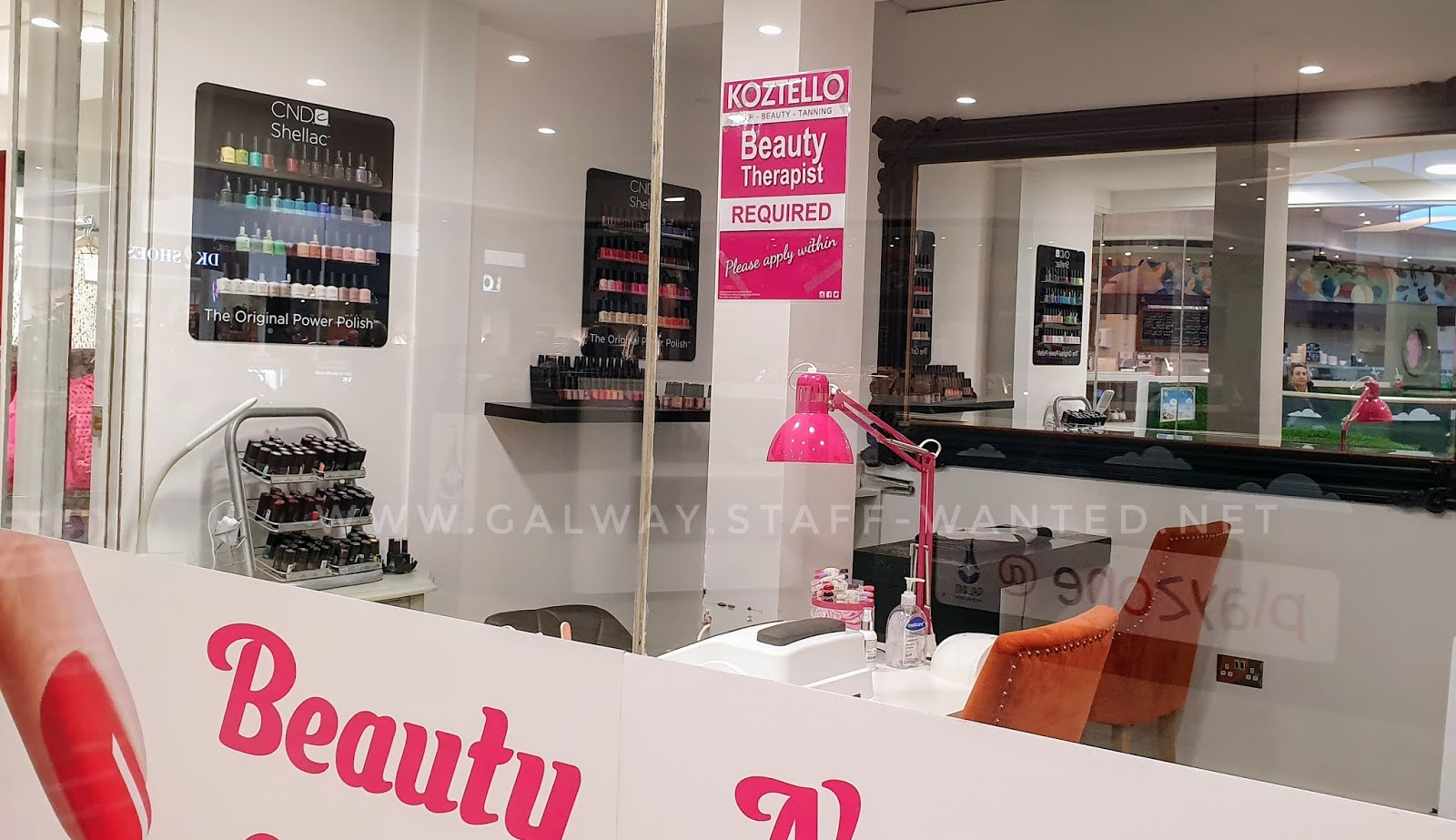 Nail salon front window in a large shopping centre, with a nail-technician workstation, selection of nail polishes and colours and a large background mirror.
