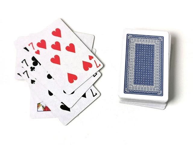 na zdjęciu stos kart zakrytych a obok niego trzy siódemki wyrzucone na stos kart odrzuconych