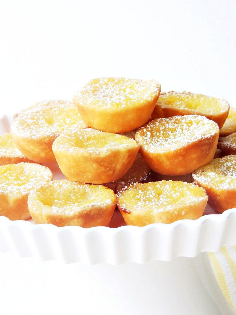 Mini Lemon Chess Pies  on a white cake plate.
