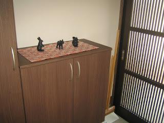 玄関のえんじ色のクロスに動物の人形