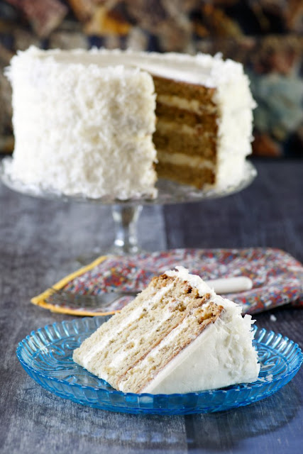 layered banana cake on stand with slice of cake served in front of it