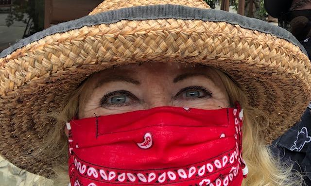 A close-up photo of a woman wearing a straw hat and a red face mask