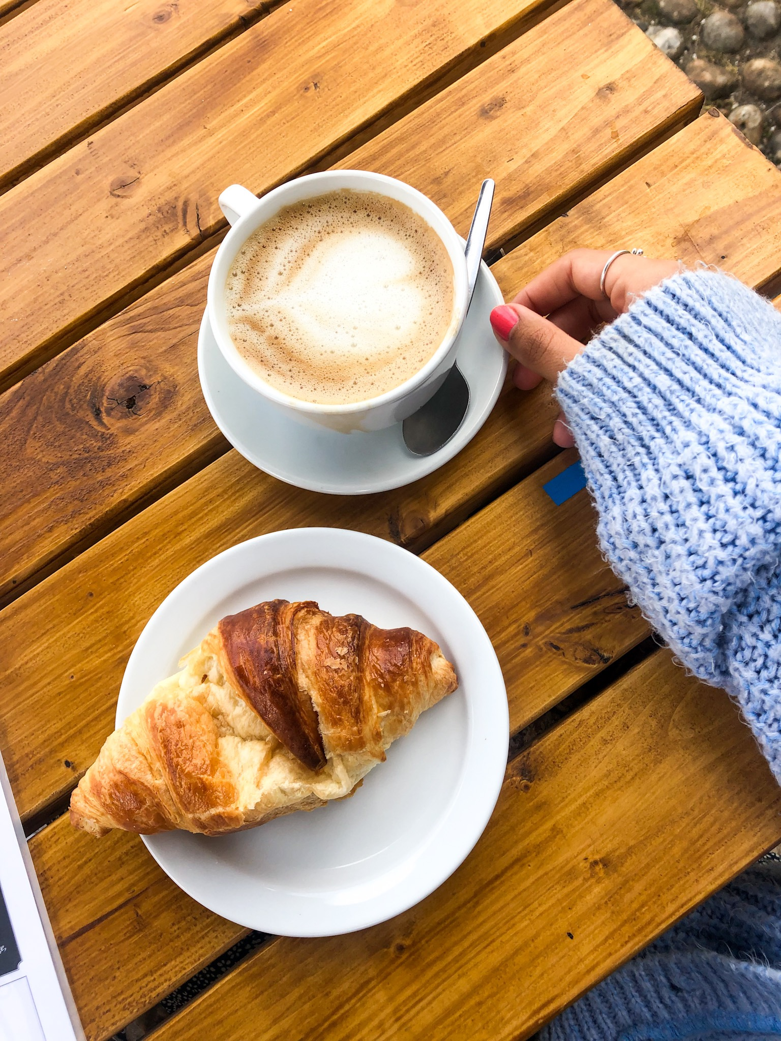 a hand is holding a coffee and croissant