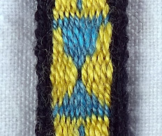 A tablet woven band that uses elongated threads as part of the pattern