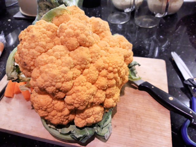 An orange cauliflower on a chopping board, surrounded by kitchen implements