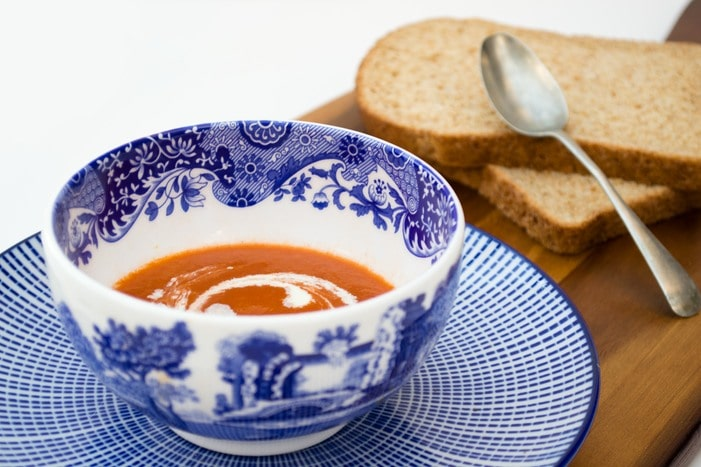 Bowl of vegan tomato soup in a blue and white bowl on a stripy blue teaplate
