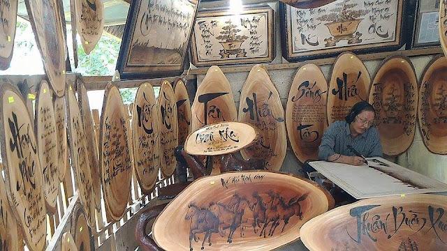Đã đặt chân đến mộ Hàn Mạc Tử xin đừng quên ghé thăm căn lều nhỏ - hàng lưu niệm của bút lửa Dzũ Kha - nghệ nhân nổi tiếng dùng bút lửa viết thơ Hàn Mạc Tử. Trong căn lều nhỏ, tủ hàng treo đầy những bức tranh, câu thơ tài hoa khắc trên gỗ làm quà kỷ niệm...