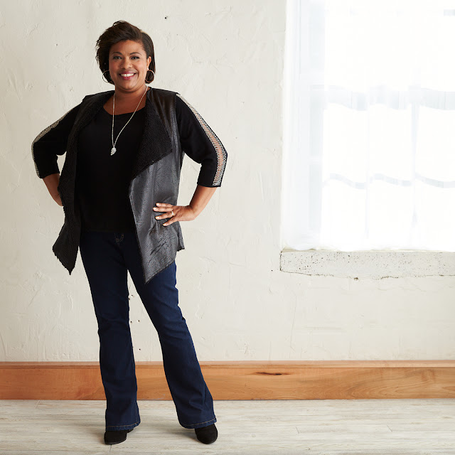 a black woman with black shirt, vest, and jeans
