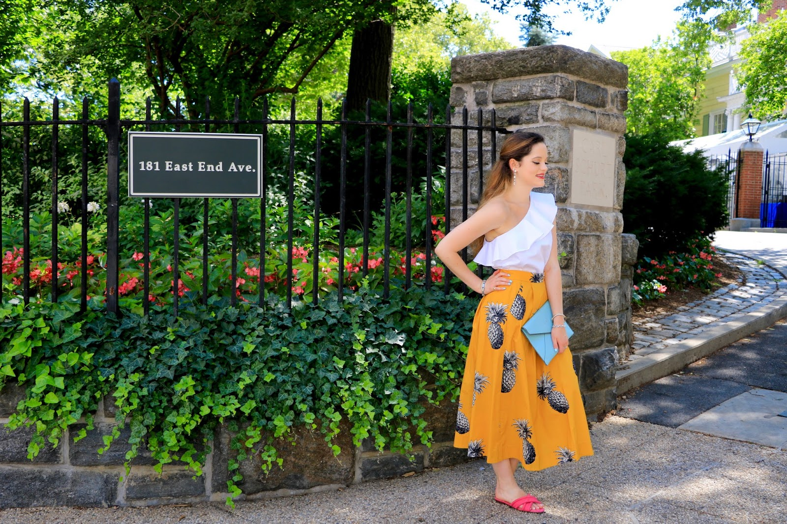 Fashion blogger Kathleen Harper in pineapple skirt, white ruffle top, and pink slides