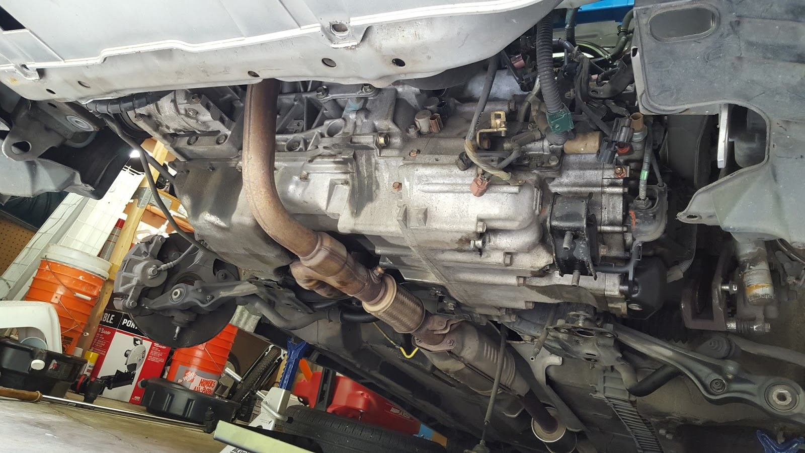 With the subframe out of the way, the transmission is supported with a jack  and all of the bolts connecting the case to the engine are removed.