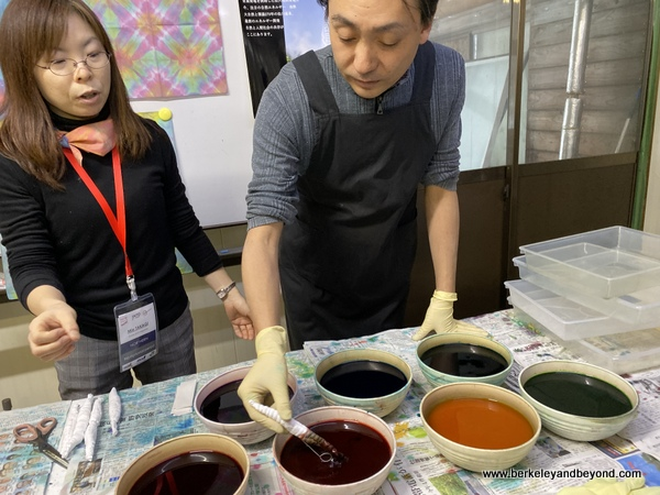 instructor demonstrates dipping tie-died cloth at Geocolor:  Hachimantai Geothermal Dyeing in Hachimantai city, Japan