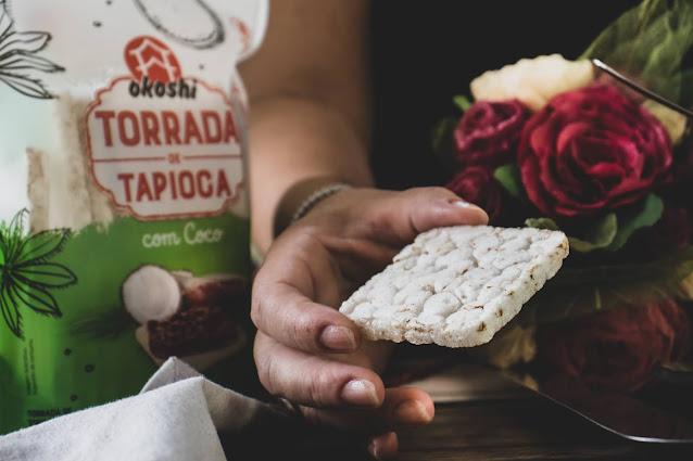 Torrada de tapioca com coco sendo segurada por mão feminina